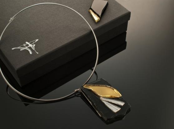 Girocollo in ottone rodiato e argento (Ø 14 cm). Gioiello (4x6x1 cm) cristallo, specchio e acciaio. Cofanetto con logo e richiamo del gioiello.