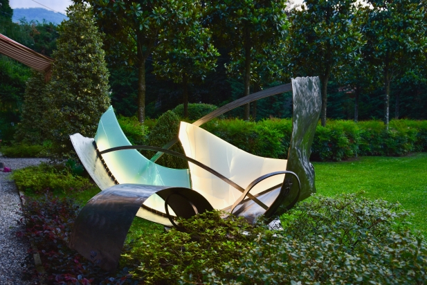 <b>Following gusts of wind</b> |  2017. Exterior light sculpture. Made from recycled stainless steel and multilayer glass, lighting LED. 240 x 120 x 220 cm. Private Park Bellagio (Lake Como) Italy.