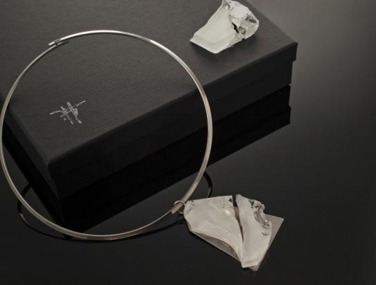 Girocollo in argento (Ø 15 cm). Gioiello (5x6x1 cm) cristallo e ottone rodiato. Cofanetto con logo e richiamo del gioiello.