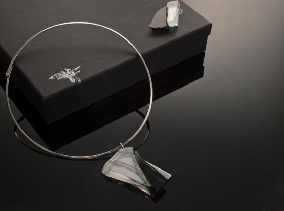 Girocollo in ottone rodiato e argento (Ø 14 cm). Gioiello (5x7x1 cm) cristallo e acciaio. Cofanetto con logo e richiamo del gioiello.