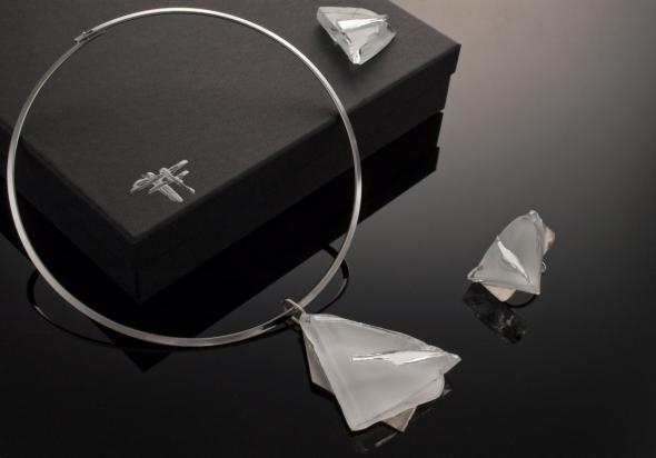 Girocollo in ottone rodiato (Ø 13 cm). Gioiello (5,5x4cm) in pasta vitrea e specchio su base in acciaio con gancio in argento. Anello (3,5x2,5cm) in pasta vitrea e specchio su base argento