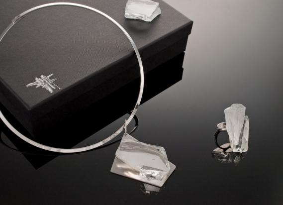 Girocollo in ottone rodiato (Ø 13 cm). Gioiello (6x4cm) in vetro e specchio su base in acciaio con gancio in argento. Anello (4x1,9cm) in vetro e specchio su base argento
