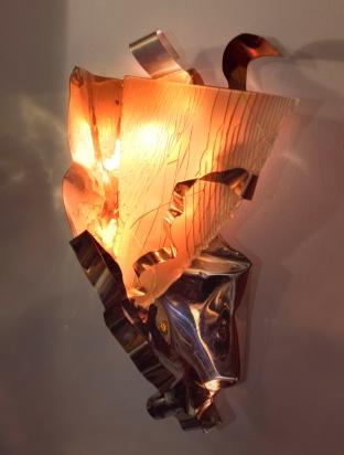 <b>Le pieghe</b> - 2018 -  48x84x38 cm | Acciaio inox e cristallo multistrato riciclati, illuminazione a led (rgbw) con variazione di colore. Opera da appendere a parete.