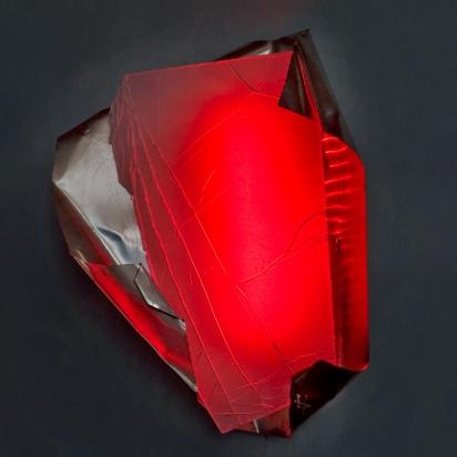 <b>Partorire sé stessi</b>, 2018.</br>  Acciaio inox e vetro multistrato di recupero, illuminazione LED di colore rosso. 46 x 58 x 33 cm.