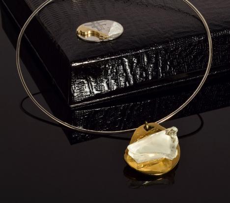 Girocollo in argento (Ø 15 cm). Gioiello (4x4,5x1 cm) cristallo e bronzo. Cofanetto con logo e richiamo del gioiello.